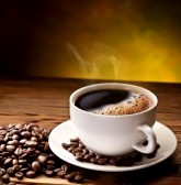 15195673-coffee-cup-and-saucer-on-a-wooden-table-dark-background